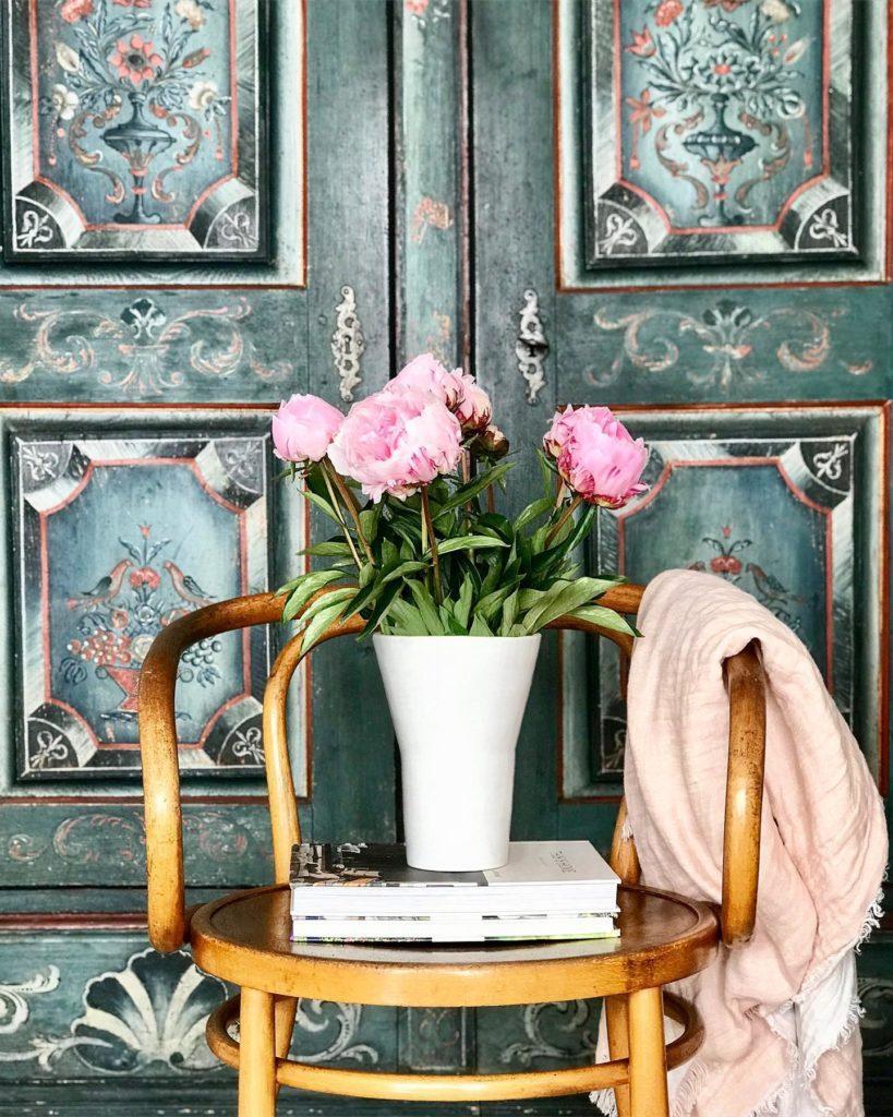 wazon z różowymi kwiatami na tle zdobionych zeilonych drzwi