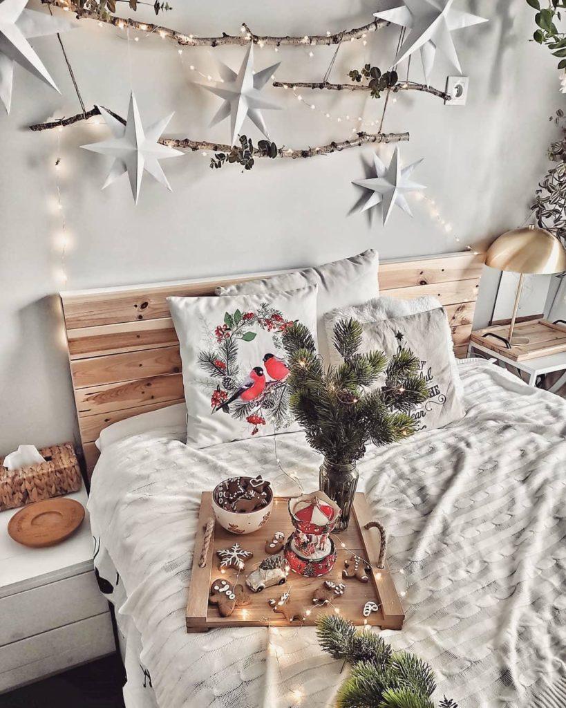 Przytulna sypialnia w stylu boho z dekoracją z patyków i gwiazdek na ścianie