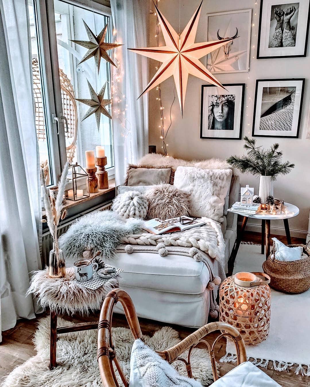 Przytulna leżanka przy oknie w stylu boho z dekoracyjnymi gwiazdami z papieru na na oknie