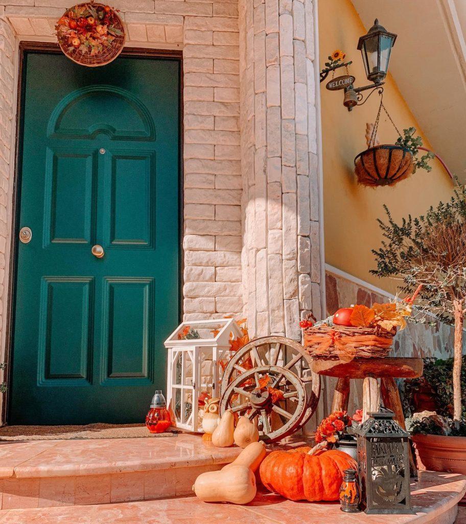 Jesienne dekoracje z dyni przed niebieskimi drzwiami wejściowymi