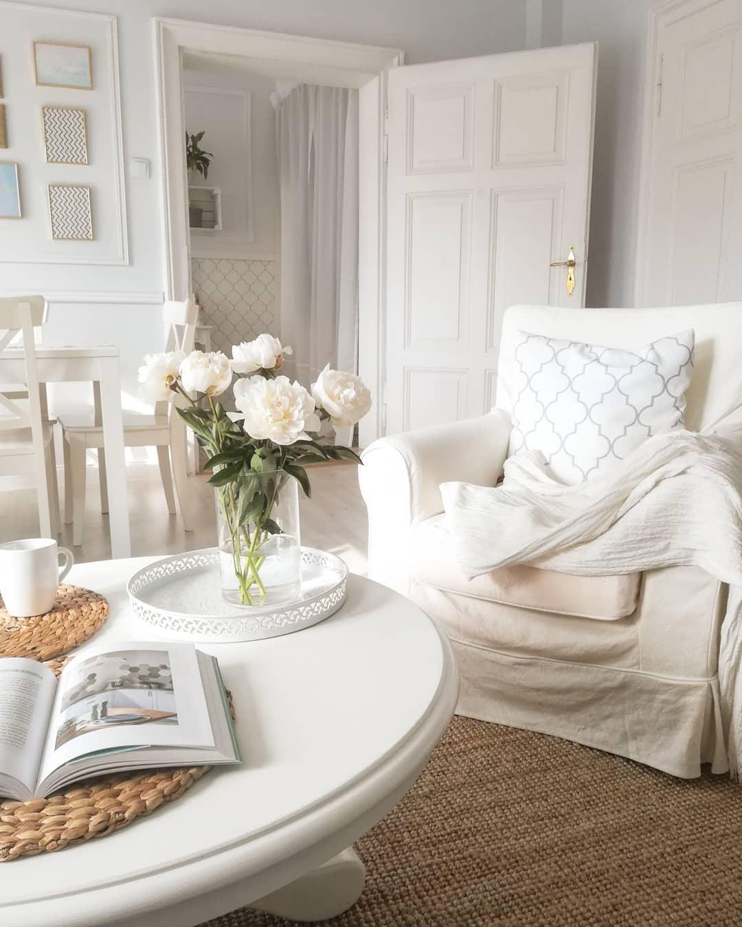 Biały fotel uszak z w stylu farmhouse w salonie z białym stolikiem kawowym z drewna i dywanem z juty
