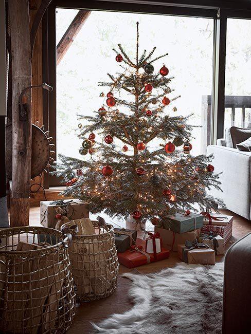 choinka w domu: Żywa choinka w salonie przy oknie, ozdobiona czerwonymi i złotymi bombkami