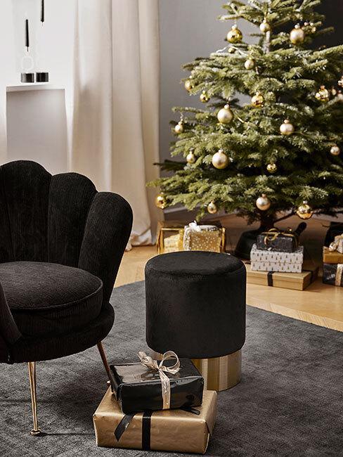Choinka minimalistycznie ustrojona złotymi dekoracjami, pod nią prezenty a przed nią fotel i puf w kolorze czarnym ze złotymi elementami
