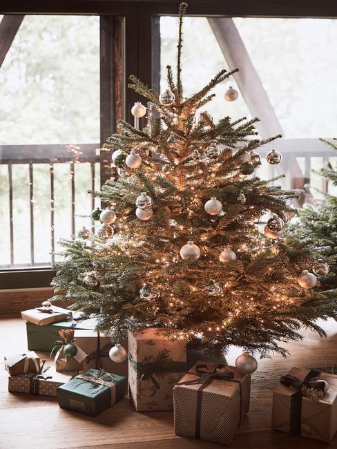 choinka w domu: Piękna szeroko choinka ozdobiona jasnymi bombkami i innymi dekoracjami