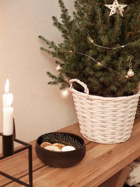 Mała choinka na konsoli w białym koszyku ozdobiona lampkami i kilkoma dekoracjami