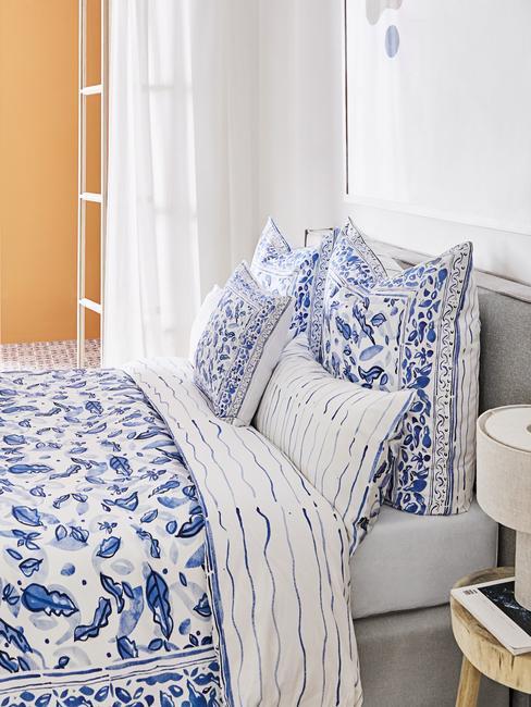 niebieska sypialnia: Pościel w biało niebieski wzór na łóżku z szarym obiciem