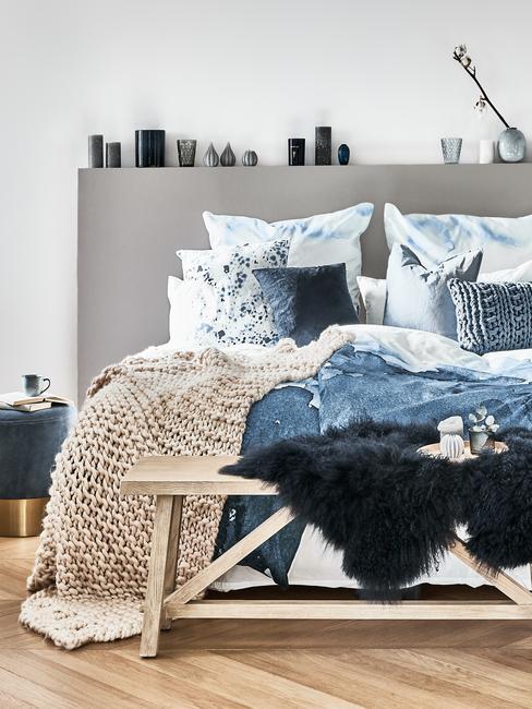 Sypialnia z tekstyliami w kolorze niebieskim, drewniana podłogą i drewniana ławką przed łóżkiem