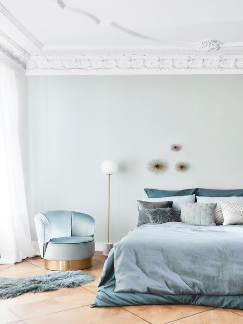niebieska sypialnia: Przestronna jasna sypialnia ze zdobionym sufitem, na łóżku tekstylia w kolorze błękitnym