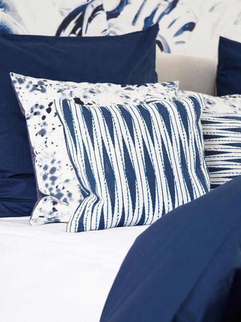 Wzorzyste poduszki, w kolorach białym i ciemnym niebieskim na łóżku z granatową pościelą