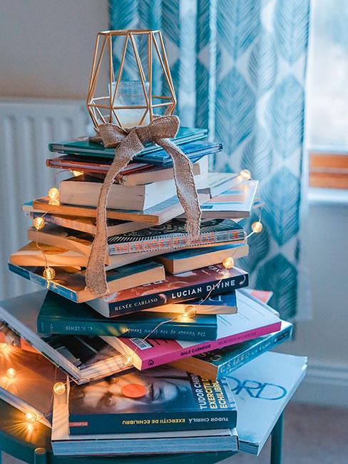 jak zrobić choinkę: Alternatywna choinka zrobiona z książek na szczycie której stoi świeczka a wokół książek owinięte są światełka