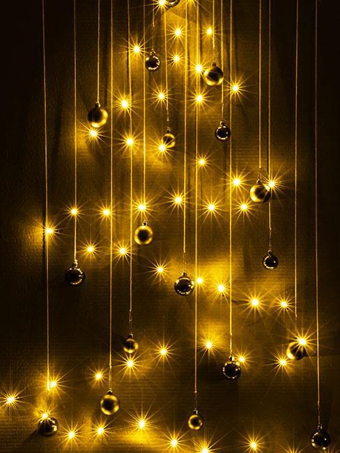 Bombki na różnej długości szurkach powieszone na ścianie przeplecione światełkami wukładającymi się w kształt choinki
