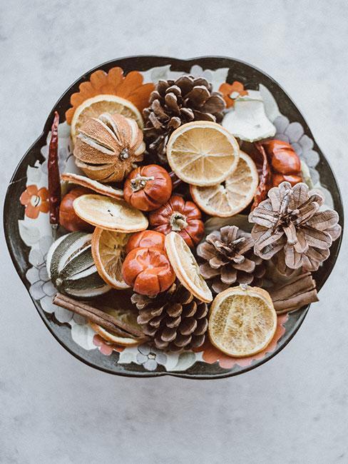jak zrobić choinkę: Miska wypełniona szyszkami i ususzonymi plastrami cytryny i pomarańczy