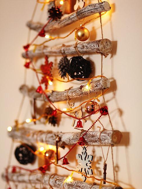 jak zrobić choinkę: choinka z patyków i sznurka powieszona na ścianie ozdobiona czerwonymi dekoracjami i światełkami