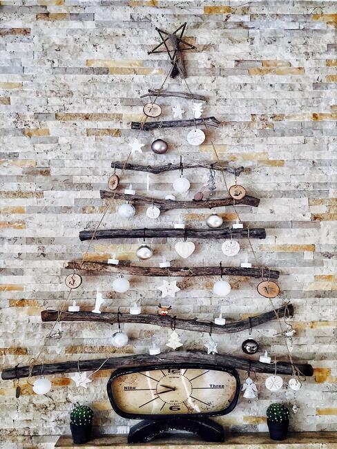 Choinka z patyków przyczepiona do ściany ustrojona białymi dekoracjami i bombkami