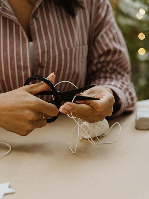 Osoba przecinająca sznurek z którego robiona będzie choinka