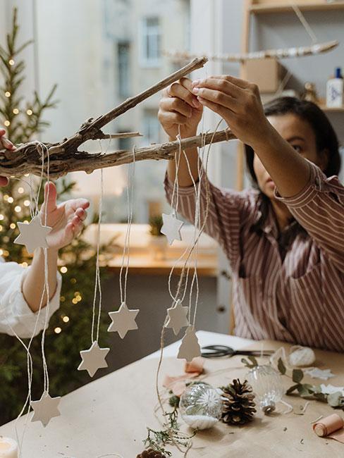 Kobieta z dzieckiem przyczepiająca do gałązki sznurki na końcach których są ozdoby