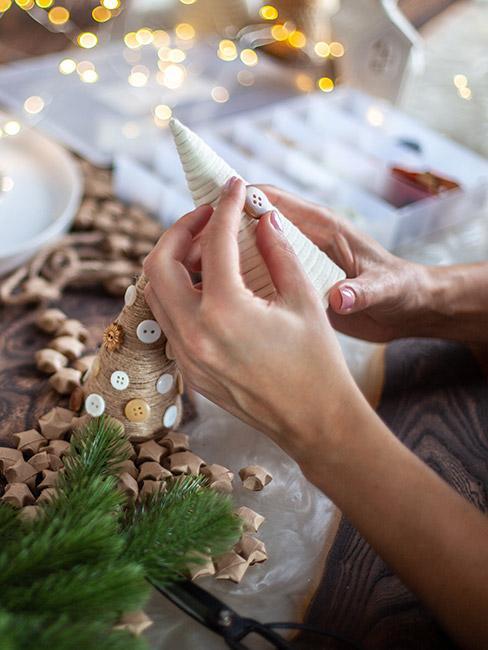 Ręce osoby ozdabiające choinkę z papieru
