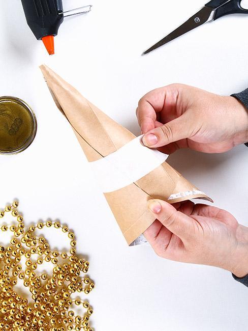 Osoba robiąca choinkę z papieru ozdobnego
