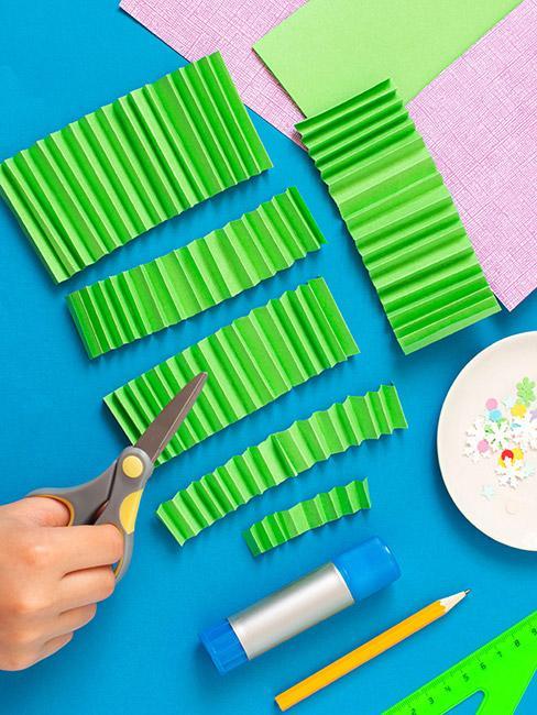 Wycięte i zwinięte w harmonijkę kawałki zielonego papieru