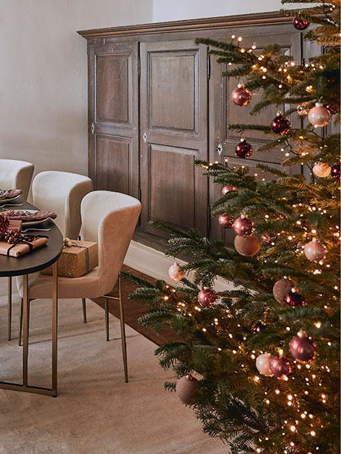 Choinka w rogu zdjęcia ozdobiona bombkami z w kolorze różowego złota, po drugiej stronie stół i białe krzesła