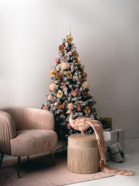 choinka czerwono złota: Choinka z ośnieżonymi sztucznym śniegiem gałązkami, z dekoracjami w kolorze złotym i różowego złota przed którą stoją beżowe fotele i dekoracyjna figurka beżowego pawia