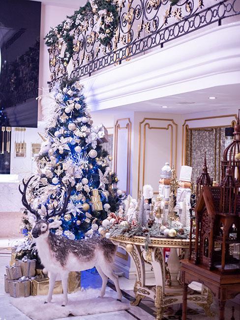 Wysoka choinka bogato zdobiona dekoracjami w kolorze białym i niebieskim