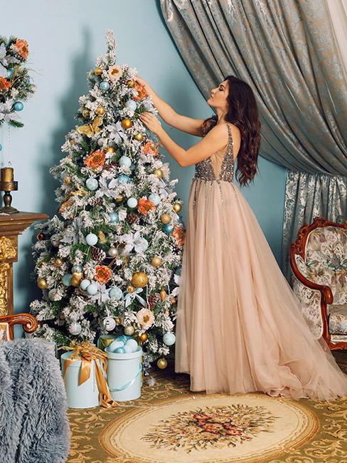 Kobieta w pięknej długiej sukni ze srebrnym gorsetem i łososiowym dołem ozdabiająca choinkę z gałązkami ozdobionymi sztucznym śniegiem