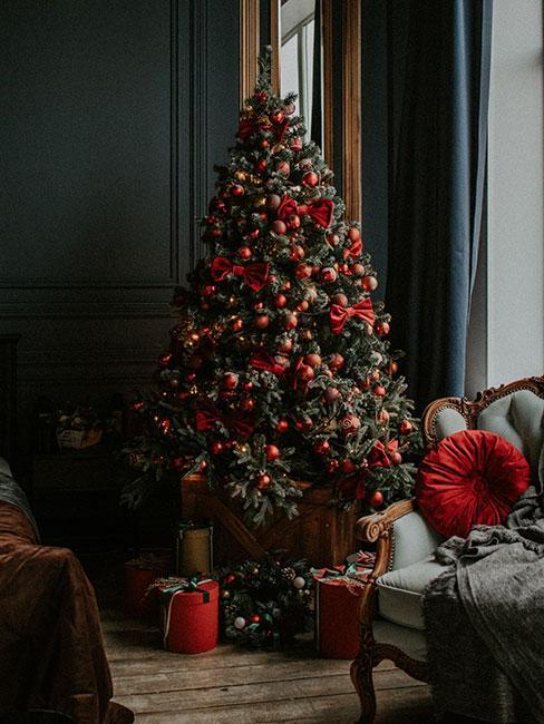 choinka czerwono złota: choinka ozdobiona czerwonymi bombkami i dużymi czerwonymi kokardami pod którą leżą prezenty