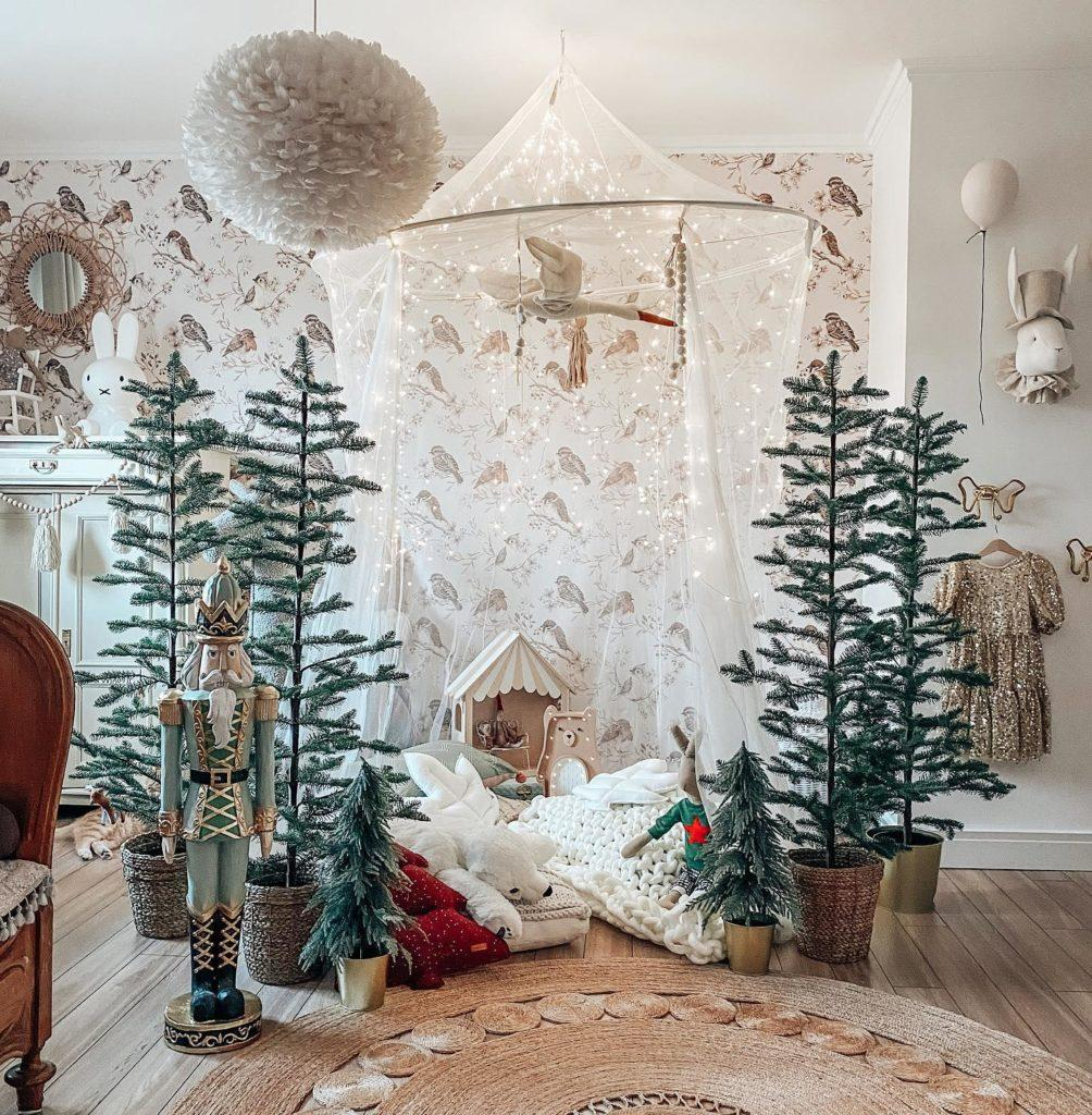 świąteczna kryjówka dla dziecka pod baldachimem otoczona choinkami