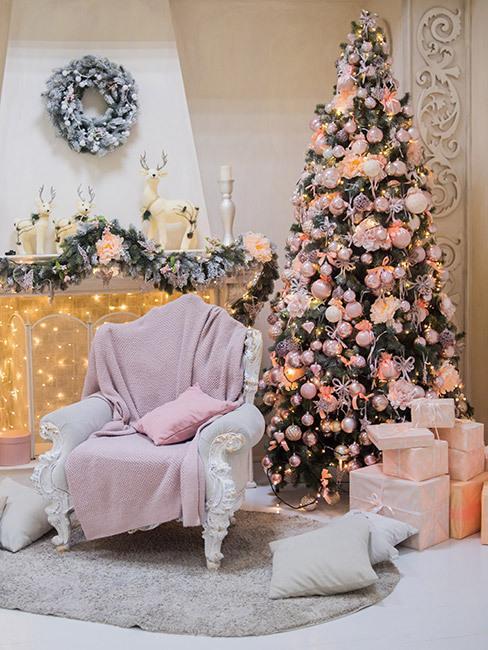 Choinka ozdobiona bombkami w kolorze różowym, obok choinki fotel przykryty kocem, w tle kominek ozdobiony lampkami