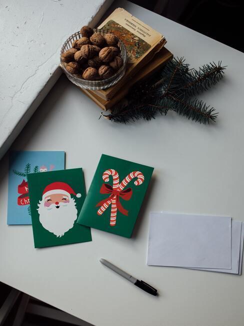 Zielone kartu z atrybutami Mikołaja na stole obok orzechów