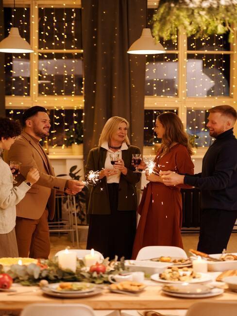 Osoby stojące przy stole z kieliszkami w ręce składające sobie życzenia
