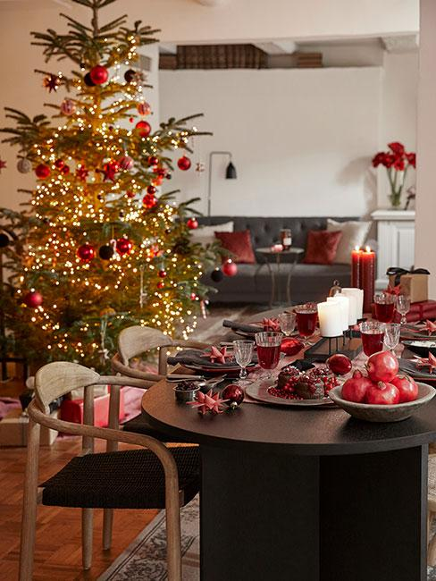 Nowoczesna jadalnia przygotowana na święta z czerwonymi dekoracjami z choinka z czerwonymi ozdobami w tle