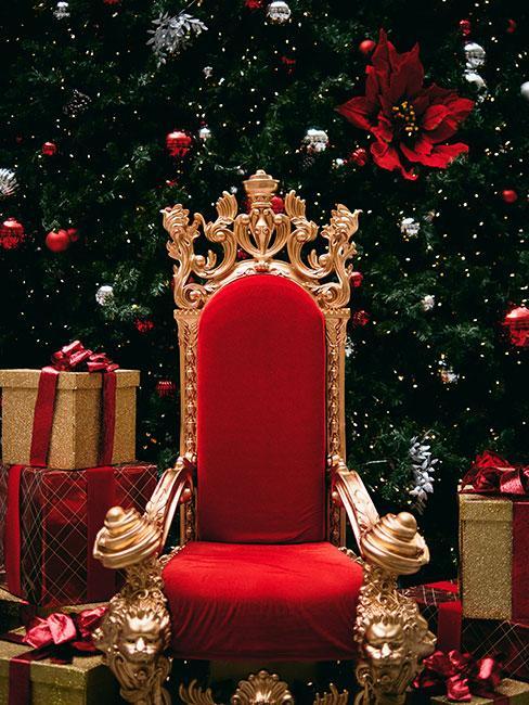 Złotoczerwony fotel z aksamitu św Mikołaja na tle choinki z czerwonymi i srebrnymi ozdobami