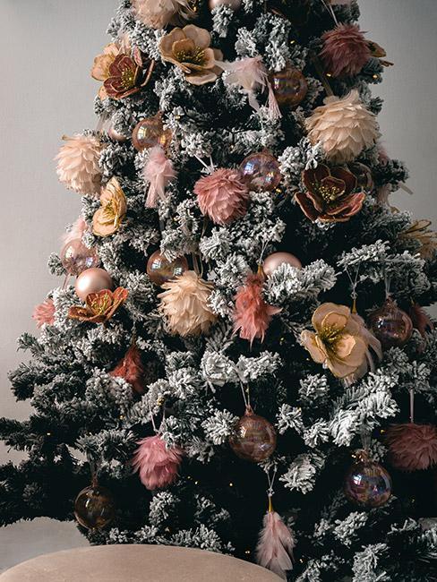 Zbliżenie na choinkę z różowymi i złotymi dekoracjami z piór i aksamitu