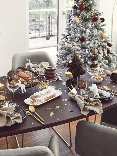 Choinka oprószona sztucznym śniegiem z miedzianymi i brązowymi ozdobami przy owalnym stole ozdobionym na wigilię