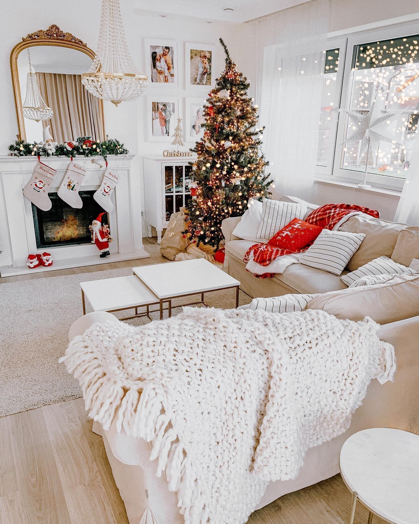 Choinka czerwono złota oprószona sztucznym śniegiem w jasnym rustykalnym salonie przy białym portalu kominkowym
