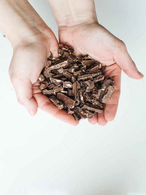 Dłonie pełne pokruszonej czekolady