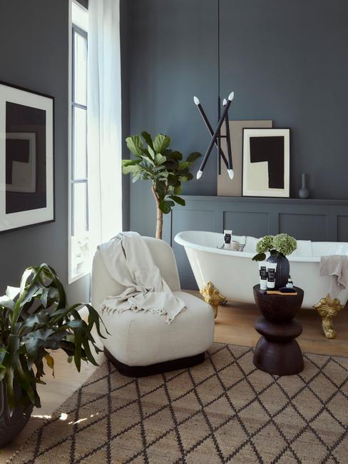 Wolnostojąca biała wanna ze złotymi nóżkami w łazience z drewnianą podłogą, popielatymi ścianami, dywanem na podłodze i fotelem