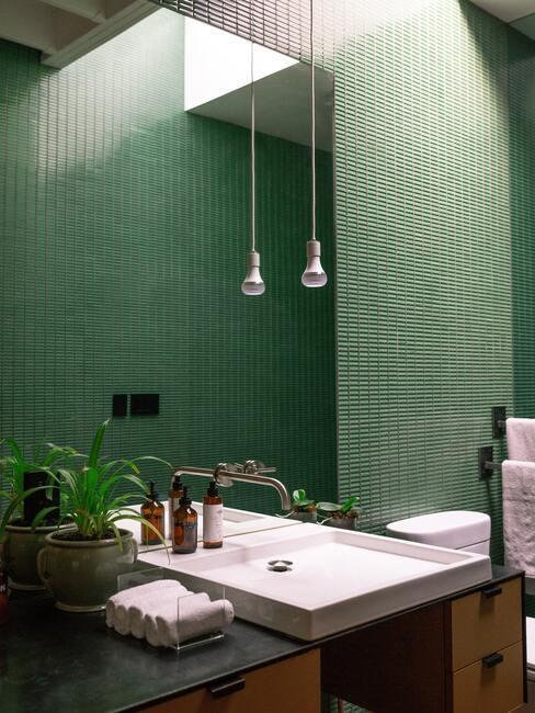 ciemna łazienka: Kafelki w łazience w kolorze butelkowej zieleni, biała umywalka i żywe kwiaty