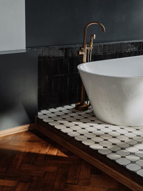 ciemna łazienka: Wolnostojąca biała wamma na biało-czarnym płytkach, obok drewniana podłoga, na ścianach ciemne płytki