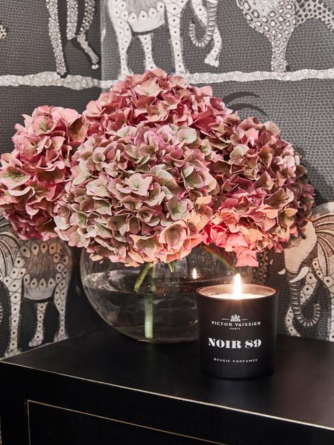 Kwiaty w przezroczystym wazonie na łazienkowym ciemnym blacie, w łazience z szarymi kafelkami w biały afrykański wzór