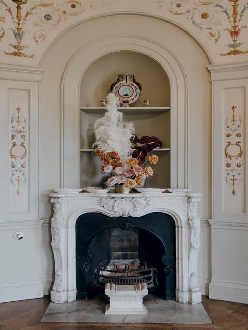 jak obudować kominek: Kominek w wiktoriańskim stylu w kolorze białym i dużą ilością zdobień