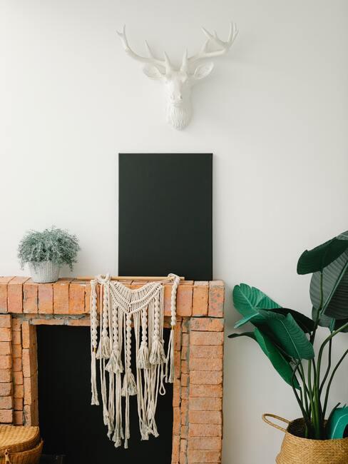 jak obudować kominek: Minimalistyczny kominek z jasnej cegły, obok żywe rośliny