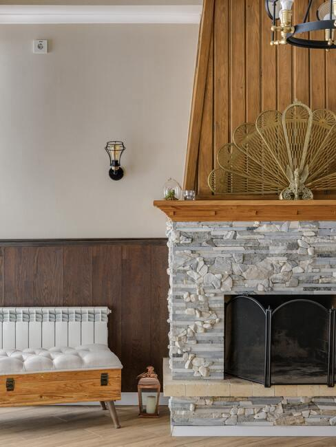 jak obudować kominek: Kominek obudowany szarymi płytkami kamiennymi, na kominku drewniana półka na której stoją ozdoby