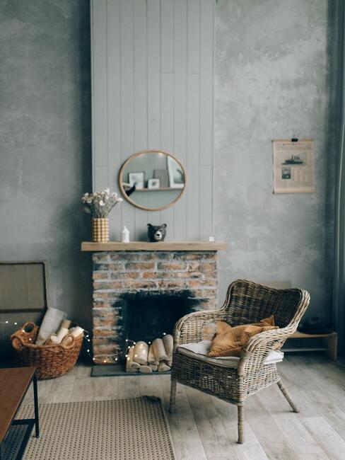 jak obudować kominek: Kominek z cegieł z drewniana półka na górze, na tle szarej ściany, przed kominkiem wiklinowy fotel