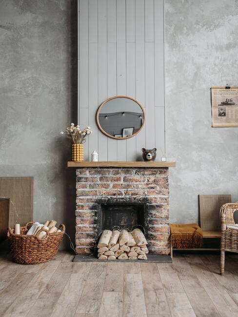 Kominek z cegieł z drewniana półka na górze, na tle szarej ściany, przed kominkiem wiklinowy fotel