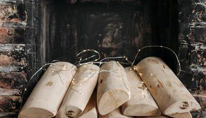 jak obudować kominek: Kominek wykonany z czerwonej cegły we wnętrzu którego poukładane jest drewno do palenia