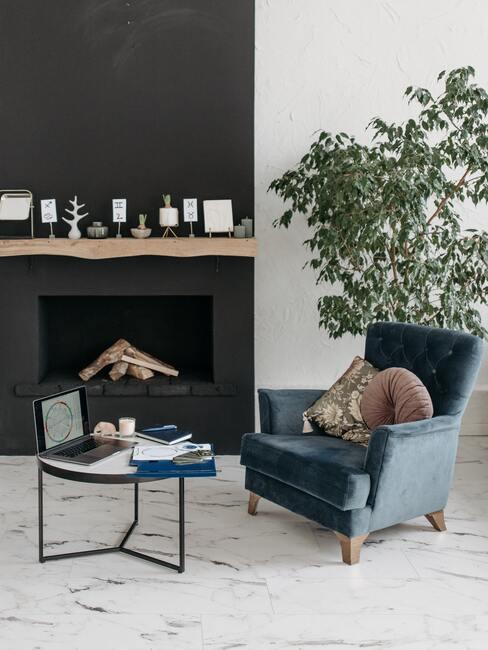 Kominek pomalowany na czarno z drewnianą półka, w salonie z marmurowa podłogą i fotelem w niebieskim kolorze