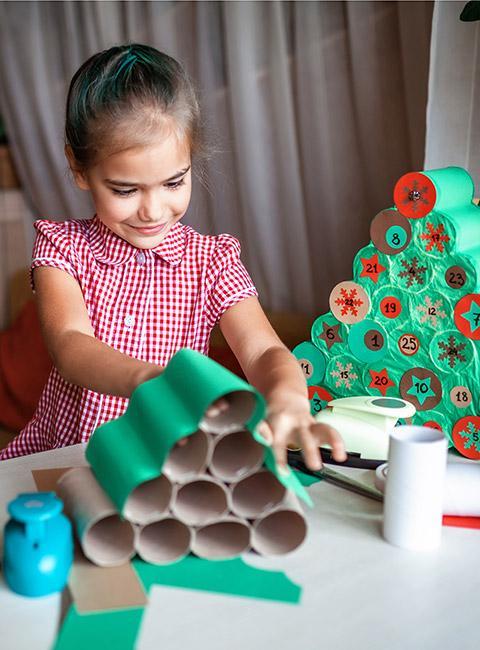 dziewczynka robiąca choinkę z rolek po papierze